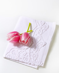 White dinner napkin and pink tulips