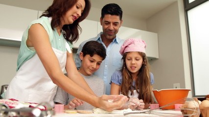 Mother kneading out dough with her family