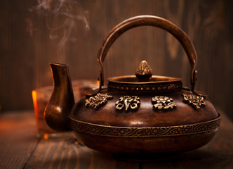 Antique iron hot tea pot on dark wooden background