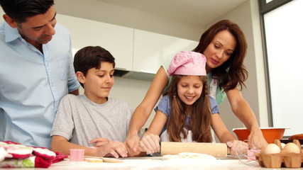 Mother helping daughter to roll out dough with her family
