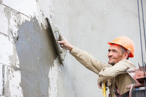 Plastering multi storey building wall of concrete blocks