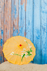 Sand and parasol in front of wooden vintage wall