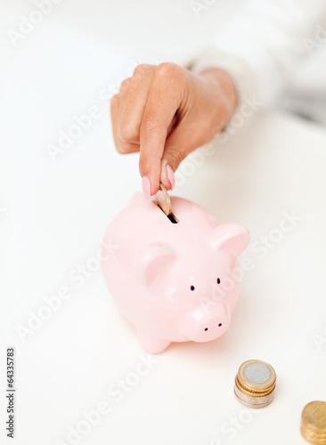 female hand putting euro coins into piggy bank
