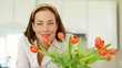 Pretty woman smelling her vase of tulips and smiling at camera