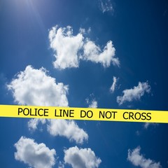 Police line do not cross sign tape on blue cloudy sky background