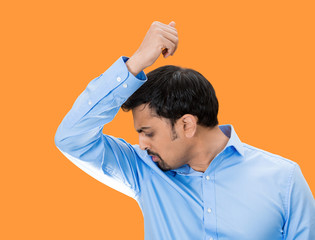 Do I stink? Young man sniffing his armpits on orange background