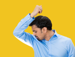 Do I stink? Young man sniffing his armpits on yellow background