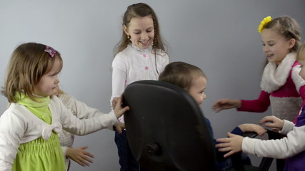 girls untwist a little boy in an office chair