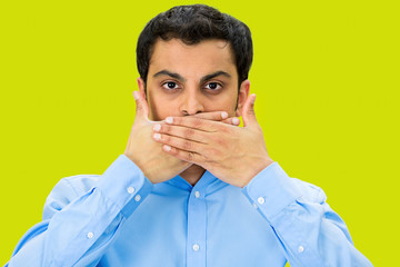 Speak no evil, man covering mouth, green background