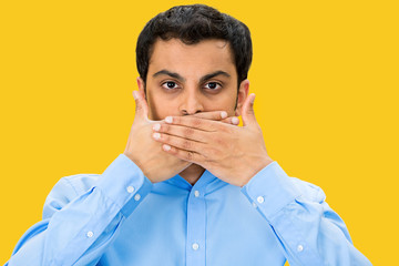 Speak no evil, man covering mouth, yellow background