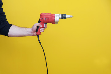 Man's left hand handling an electric drilling machine, isolated.