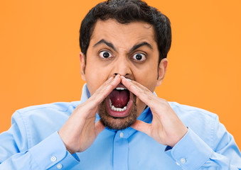 Yelling angry man isolated on orange background