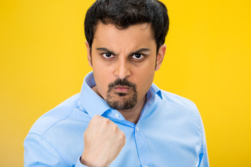 Portrait angry man with fist up, isolated yellow background