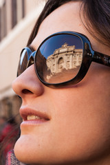 Model with Trevi's fountain reflected on sunglasses
