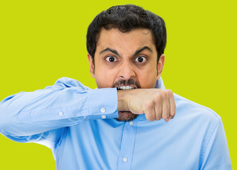 Crazy, upset young man Biting his arm, green background
