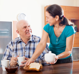 mature woman serving breakfast to husband