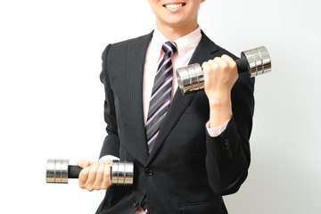スーツを着てダンベルを使って筋力トレーニングをする男性