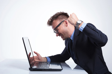 business man punches his laptop