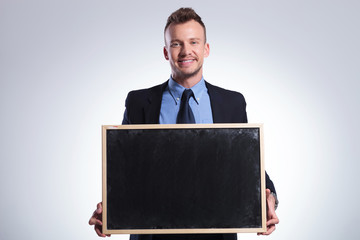 business man holds a small chalkboard