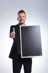 business man holds a blackboard and shows ok
