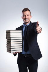 business man with many books shows ok
