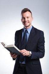 business man smiles with book in hand