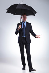business man smiles at you with umbrella