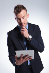 pensive business man looks at tablet