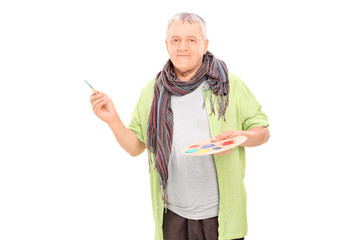 Mature male artist holding a color pallet