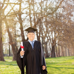 Mature college graduate holding a diploma in park