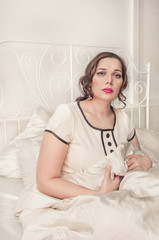 Sad plus size woman sitting in the bed