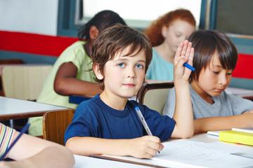 Kind hebt Hand in Grundschule