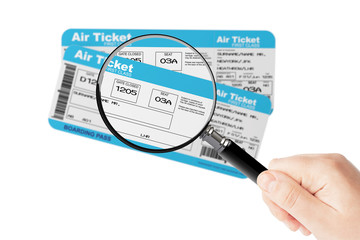 Airline boarding pass tickets with magnifier glass in hand
