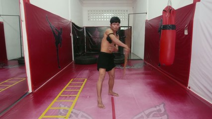15of20 Asian man training kick boxing in gym as fighter
