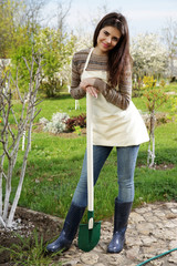 Woman standing with shovel in the garden