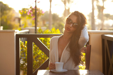 Cute young brunette resting with cup of coffee