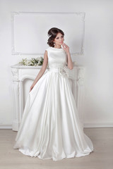 Beautiful bride woman posing in magnificent dress over white wal