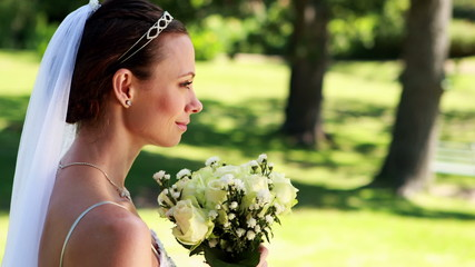 Smiling bride smelling her bouquet