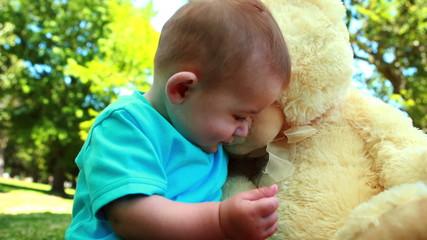 Cute baby boy playing with teddy bear