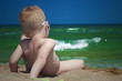 Little boy on the beach. child sitting in sand.Summer.sea.sky