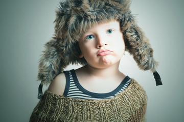 child in fur Hat.fashion winter style.little funny boy.children