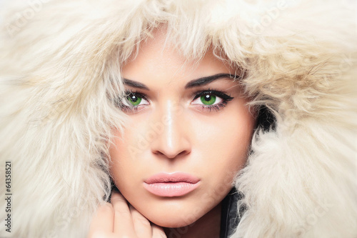 young beautiful woman with fur. white fur hood. winter girl