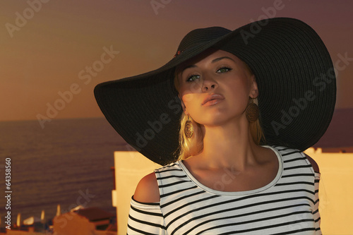 Beautiful blond woman in hat.Sunset.roof.sea.Summer