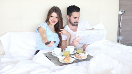 Young Couple Watching TV on the Bed
