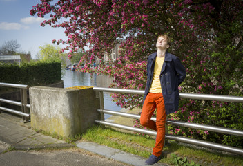 Young attractive stylish blond man against canal background.