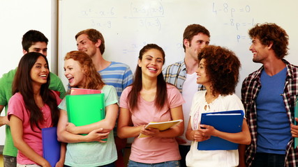 Students standing in classroom giving thumbs to camera