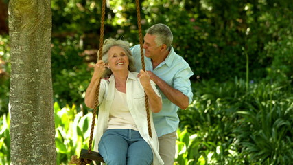 Senior man pushing his wife on a swing