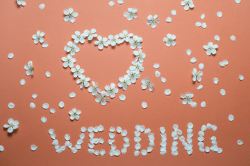 Word WEDDING and a heart as a symbol of love made of flowers.