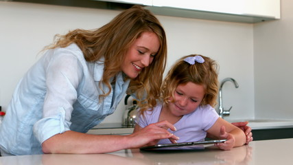 Mother using tablet with her daughter in the kitchen