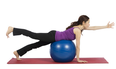 Young woman exercising with a pilates ball